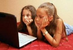 Niñas mirando una computadora acostadas
