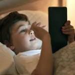 niño acostado con tablet